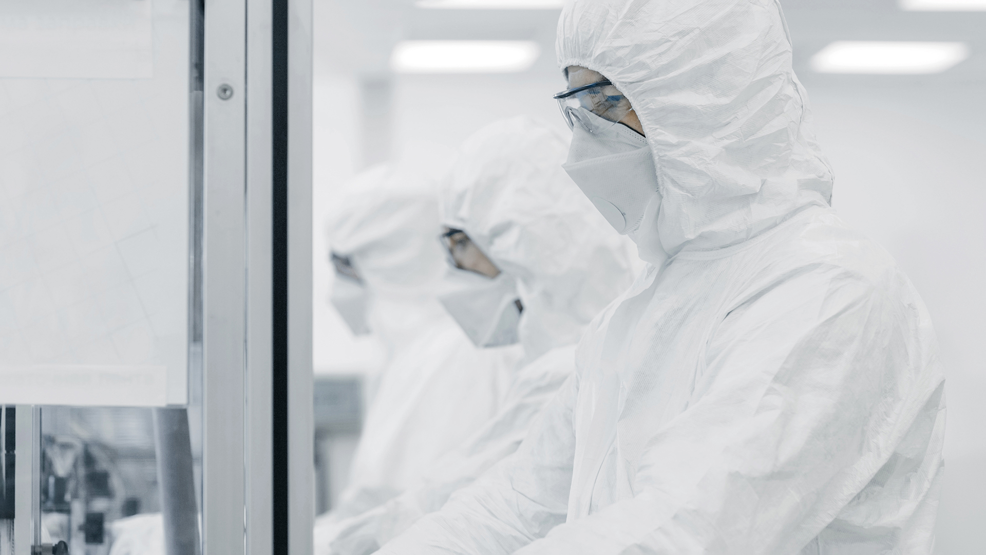 Three persons in cleanroom suits